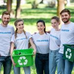 young-volunteers-with-green-recycling-boxes-for-trash-standing-in-park.jpg